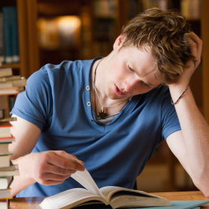 Man läser bok vid ett bord i ett bibliotek.