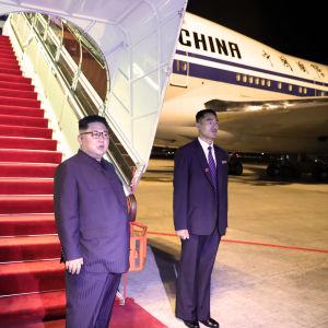 Kim Jong-Un står och vinkar utanför ett Air China flygplan i Singapore.