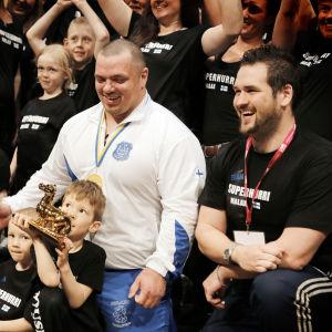 """En busslast Malaxbor, inklusive barnen Felix och Viktor som håller i pokalen och Kristoffer """"Koffen"""" Nykopp längst till höger, följde Fredrik Smulters framgångar under fjolårets VM i Sundsvall."""