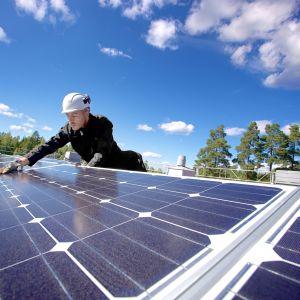 Forskningsassistenten Miguel Lavado installerar solpaneler på taket till Villmanstrands tekniska universitet