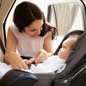 Kvinna spänner fast barn i bilbarnstol.