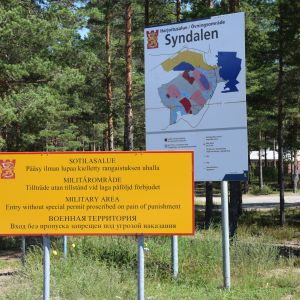 Två skyltar, den ena är karta över Syndalens övningsområde och den andra en skylt där det står - militärområde - tillträde utan tillstånd vid laga påföljd förbjuden.