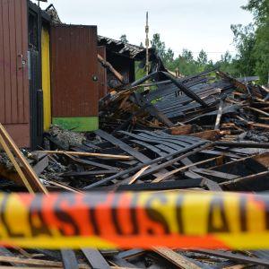 Brandskadat bråte efter branden vid Sipoonlahden koulu i Söderkulla. I förgrunden räddningsverkets avspärrning.