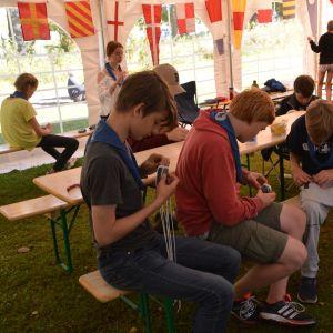 En grupp unga scouter sitter vid ett bord och göra reparbeten.
