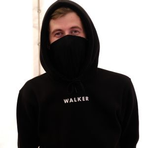 Den norsk-brittiska artisten och DJ:n Alan Walker sitter iklädd svart huvtröja och en rånarluva som täcker nedre delen av ansiktet.