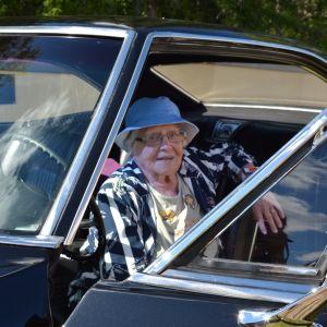 Äldre dam sitter i en Chevrolet.