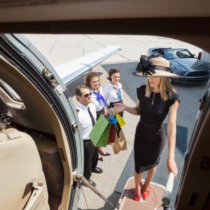 En kvinna i klänning stiger ombord på ett privatplan.