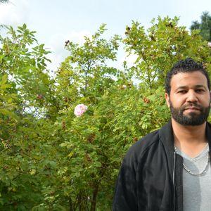 Man med utblommad rosenbuske i bakgrunden.