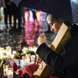 Ung kvinna med mörkt hår spelar på kanteleliknande instrument vid gravljusen och blommorna på Åbo salutorg efter knivdådet den 18.8.2017