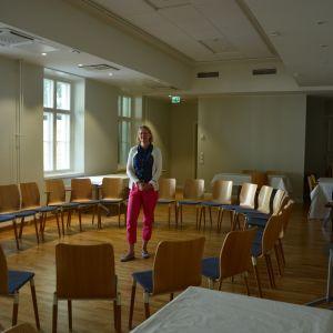 Ljus kvinna i röda byxor och vit tröja på blått står i mitten av en sal med stolar i ring och vackra gamla fönster