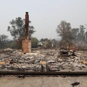 Ruinerna av ett hus efter markbränder i Sonoma i norra Kalifornien. Bara skorstenen står kvar efter att huset brandhärjades.