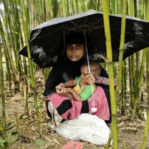 En rohingyaflykting har tagit skydd under ett paraply med sin baby i flyktinglägret Thangkhali, Coxbazar, Bangladesh 12.10.2017.
