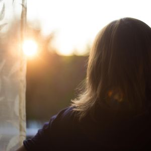 Kvinna tittar ut genom fönstret.