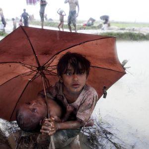 En liten flicka bär på sitt syskon medan hon vadar över en flod på väg till flyktingläger i Bangladesh.