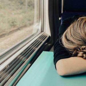 Väsynyt nainen junassa.