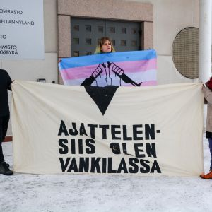 """Tre personer håller i en vit banderoll med texten """"Ajattelen - siis olen vankilassa""""."""
