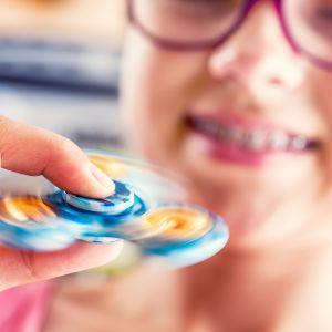 tyttö leikkii fidget spinnerillä