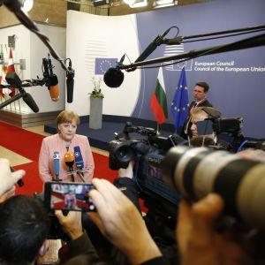 Tysklands förbundskansler Angela Merkel omringad av journalister i Bryssel.