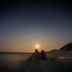 kaksi hahmoa istuvat huput päässä hiekalla auringon laskiessa