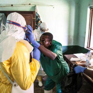 Hälsovårdare iklädd skyddsdräkt förbereder sig på att undersöka patienter som kan ha smittats av ebola. Sjukhus i Bikoro 13.5.2018.