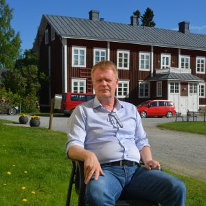 Carl-Johan Strömberg, direktör för Lagmansgården, sitter på en stol under strålande solsken.