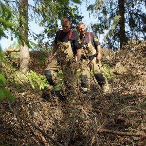 två brandmän går i skogen