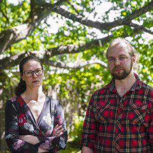 Linda Siik (t.v.) och Jesse-Pekka Rautiainen under ett träd på gården av deras hem i Marudd i Helsingfors.