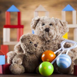 En nalle och några leksaker på golvet.