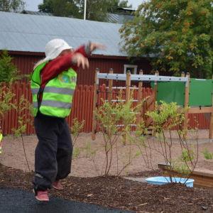 En flicka hoppar och kastar en boll vid daghemmet Touhula i Borgå