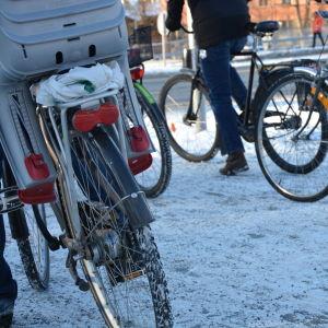 Flera cyklister väntar vid vägen i centrala Åbo.