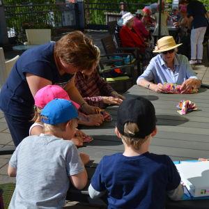 Barn och seniorer viker servetter.