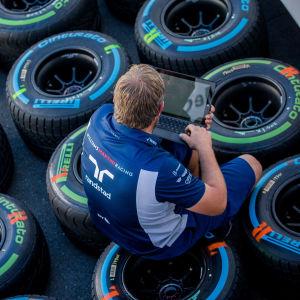 En F1-ingenjör sitter på däck.