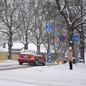 En kvinna väntar på att få gå över Alexandersgatan i Borgå.