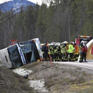 En buss ligger på sidan i ett dike. Intill står räddningspersonal och ett tält där busspassagerare vårdas.