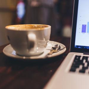 En kaffekopp bredvid en laptop på ett bord.
