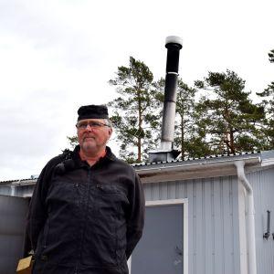 På bilden Rune Råberg som är sotare och i bakgrunden en skorsten.
