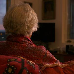 Vanhus istuu nojatuolissa selin.
