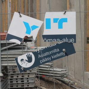 En söndrig skylt på ett staket som omgärdar en byggplats.