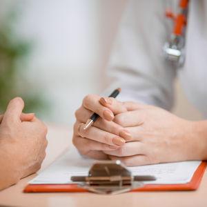 Närbild av händerna av en läkare och dennes patient. De sitter mot varandra och samtalar.
