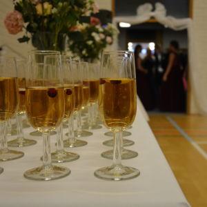 Glas med skumvin i förgrunden, festligt klädda ungdomar i bakgrunden.