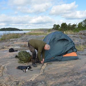 Patrik Berghäll sätter upp ett tält