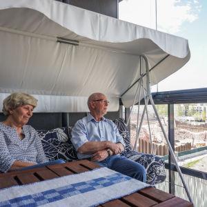 Britta (till vänster) och Matti Krank sitter på sin balkong, varifrån byggarbetsplatsen vid Lippulaiva syns.