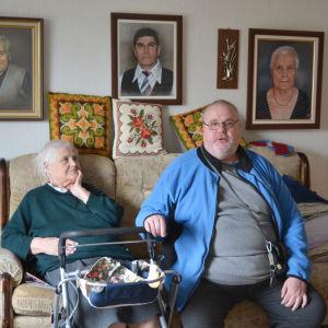 Eila och sonen Ove sitter tillsammans i hennes soffa, Eila har en rollator