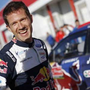 Sébastien Ogier står vid sin bil under VM-rallyt i Portugal.
