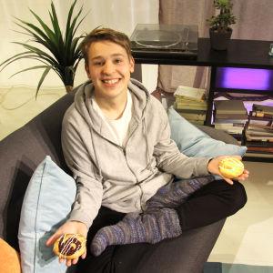 Jakob Norrgård sitter i en soffa med en bulle i varsin hand.