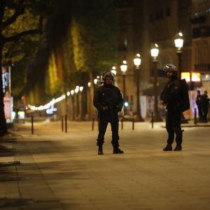 Två tungt utrustade poliser står på en ödslig gata i Paris, efter skottlossningen på Champs-Elysées.