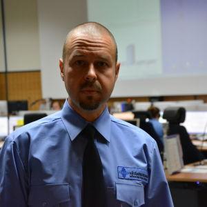 Matias Snellman bär en blå skjorta, svart slips. Han står med nödcentralens jourrum i bakgrunden.