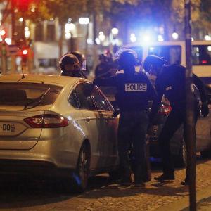 Ett flertal tungt utrustade poliser står vid två parkerade bilar, i bakgrunden blåljus.