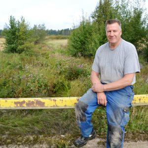 Ralf Koho sitter på ett räcke på¨en bro som går över Hardombäcken i Lovisa.