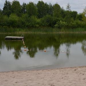 en bild över toby simgrop med stranden, vattnet, grönska och en brygga